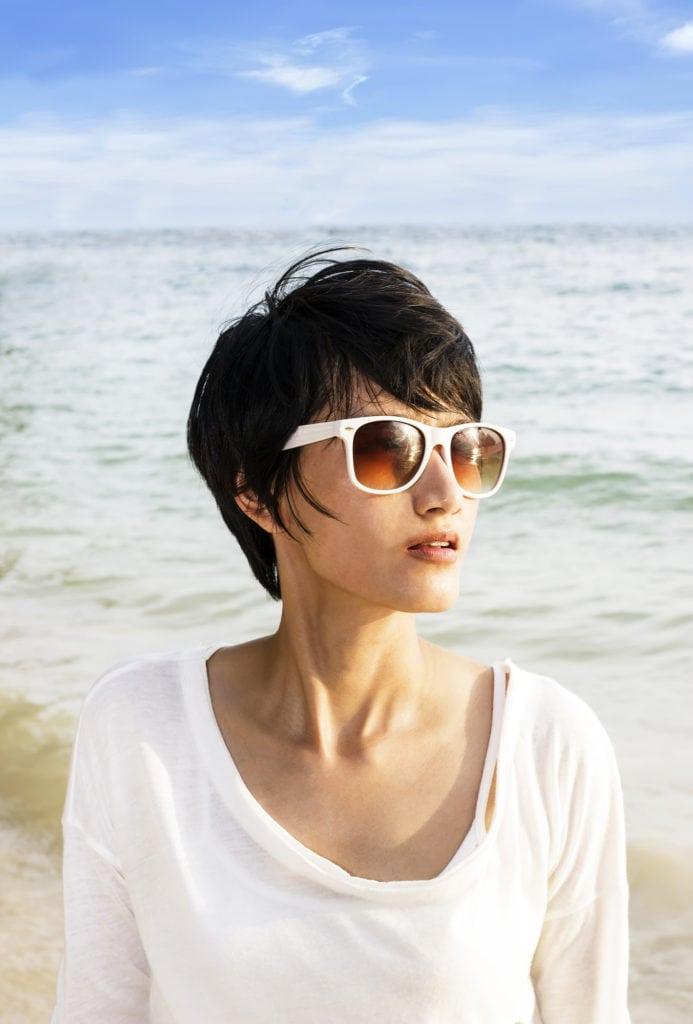 Short hair Asian woman on the beach with sunglasses and short hair cut